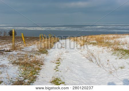 Winter Landscape With Earth Road Leading Down To Kakhovka Reservoir Located On The Dnipro River Near