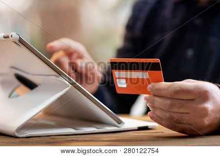 Shopping On Tablet Using His Credit Card And Having His Coffee In Office Room