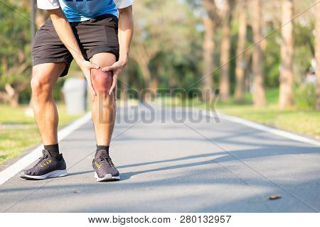 Young Fitness Man Holding His Sports Leg Injury. Muscle Painful During Training. Asian Runner Having