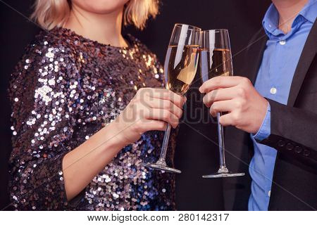 Photo of woman in brilliant dress and men with wine glasses with champagne on black background