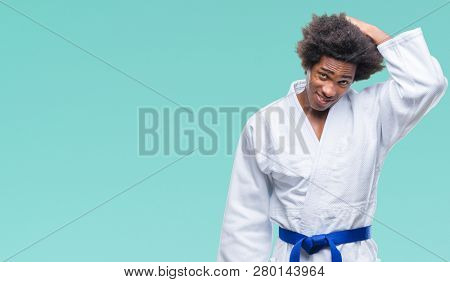 Afro american man wearing karate kimono over isolated background confuse and wonder about question. Uncertain with doubt, thinking with hand on head. Pensive concept.