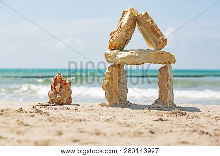 House Made Of Stones Against The Sea, Background Sea. Sea Stones On The Background Of The Sea