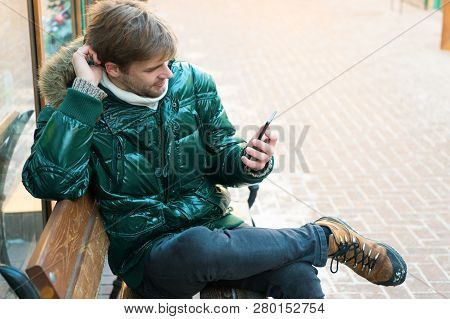 Hipster Use Smartphone On Winter Day. Man Handsome Hold Smartphone. Guy Sit Bench Interact Smartphon