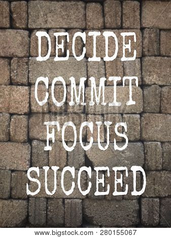 Motivational And Inspirational Quote - Decide, Commit, Focus, Succeed. Written On A Blurred Backgrou