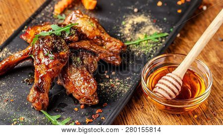 The Concept Of Indian Cuisine. Baked Chicken Wings And Legs In Honey Mustard Sauce. Serving Dishes I