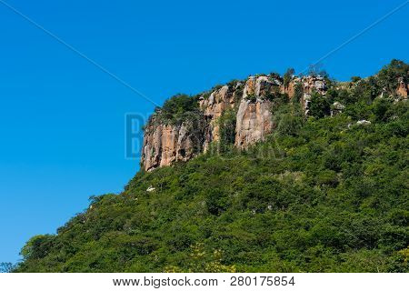 A rocky outcrop rising out of dense green forest against a blue sky in the Umgeni Valley Nature Reserve, Kwa-Zulu Natal, South Africa. poster
