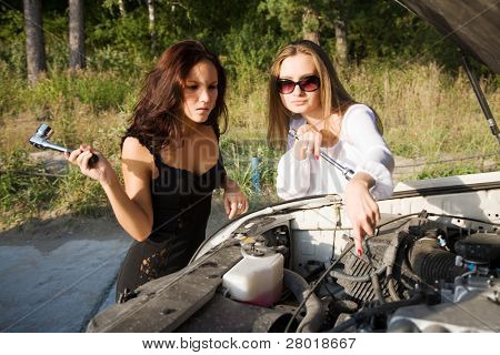young beauty girl try to repair big car