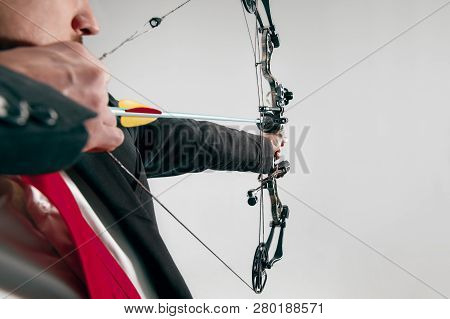 Businessman aiming at target with bow and arrow isolated on gray studio background. The business, goal, challenge, competition, achievement, purpose, victory, win, clarity, winner and success concept poster