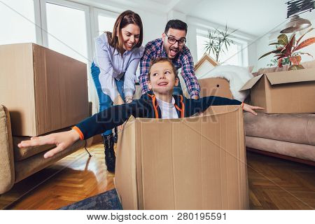 Happy Family Moving Home With Boxes Around, And Having Fun.