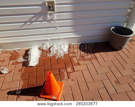Outdoor Hose Spigot With Ice And Red Bricks In Winter