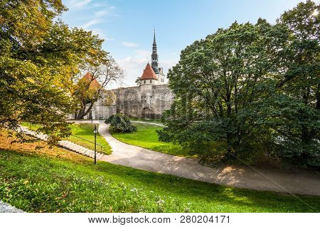 The Tower And Spire Of St. Nicholas Church Rises Above The Medieval Town Walls Of Tallinn, Estonia