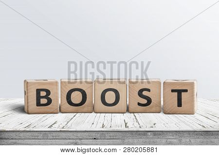 Boost Sign On A Wooden Table In A Bright Room With A Light Blue Wall