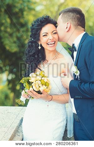 Groom Kiss Happy Bride With Bouquet. Woman And Man Smile On Wedding Day. Wedding Couple In Love. New