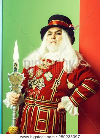 Proud Senior Man Beefeater Yeomen Warder Or Male Royal Guard Bodyguard In Red Uniform With Spear On