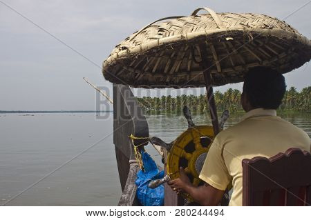 Backwaters, India - August 24: Man Driving A Houseboat On August 24, 2011 In Backwaters, India. Back
