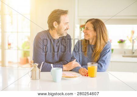 Beautiful romantic middle age couple having healthy breaskfast in the morning at home