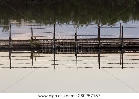 This A Floating Bridge Across A Small Pond. It Has Ropes For Rails. I Thought This Image Had A Lot O