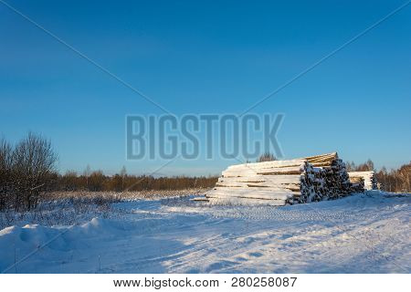 A Large Pile Of Logs Covered With Snow At The Edge Of The Road.