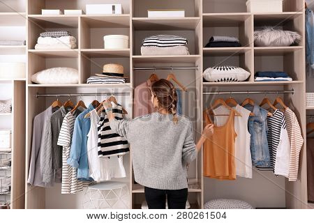 Woman Choosing Outfit From Large Wardrobe Closet With Stylish Clothes And Home Stuff
