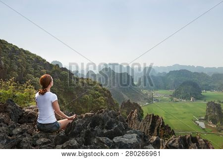 Young Woman Keep Calm And Meditates While Practicing Yoga On The Top Of The Hill With Beautiful View