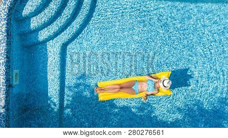 Beautiful Young Girl Relaxing In Swimming Pool, Swims On Inflatable Mattress And Has Fun In Water On