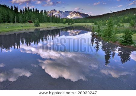 The sun shines tops of distant mountains, clouds above lake and fur-trees on coast
