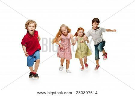 Group Of Fashion Cute Preschooler Kids Friends Running Together And Looking At Camera On A White Stu