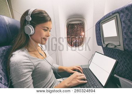 Plane passenger business woman professional working in airplane cabin during flight with in-flight wifi typing writing on tablet computer listening to music with headphones. Young Asian traveler.