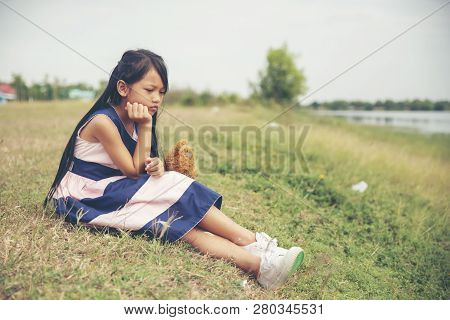 Sad Child With Family Problem,hugging Teddy Bear In Park.asian Little Girl Sitting With Best Friends