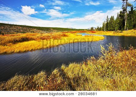 The picturesque twisting small river, fenny coast and yellow autumn grass