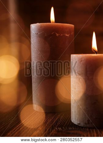 Two Burning Candles With Festive Golden Light Effects On Dark Wood For Special Moments