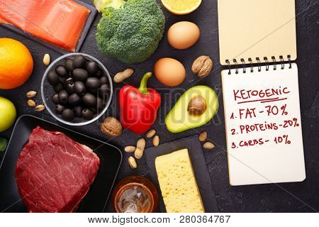 Photo of products for diet, notebook on black stone table.