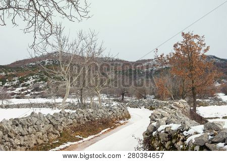 Winter Country Road. Snowy Landscape Of The Bosnian Countryside On A Cloudy Day. Bosnia And Herzegov