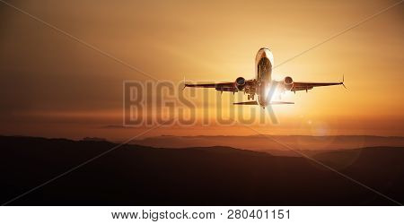 modern aircraft while landing against a sunset