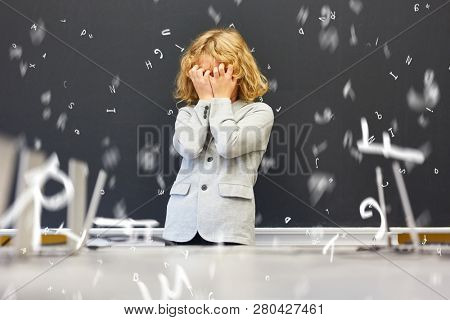 Child with dyslexia in front of blackboard in elementary school