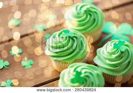 st patricks day, food and holidays concept - close up of green cupcakes and shamrock on wooden table