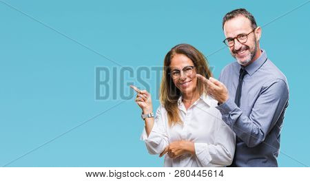 Middle age hispanic couple in love wearing glasses over isolated background with a big smile on face, pointing with hand and finger to the side looking at the camera.