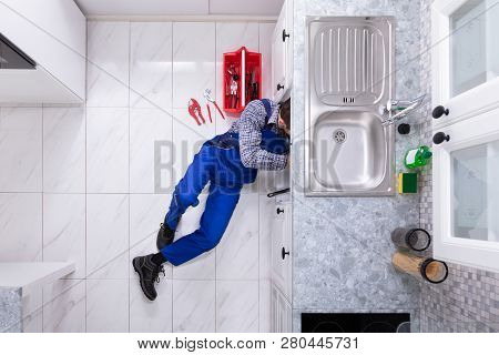Young Male Plumber Repairing Sink Pipe With Adjustable Wrench
