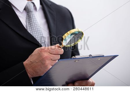 Close-up Of  Businessman Analyzing Document  Through Magnifying Glass At Workplace