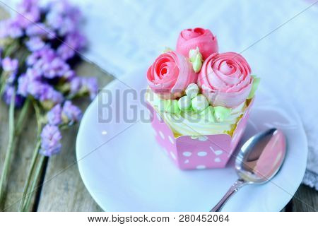 Vanilla Cup Cake And Spoon On A Plate With Cup Cake In Background And Flower  As Decoration For Vale