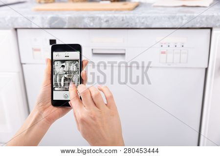 Woman Operating Dishwasher With Mobile Phone