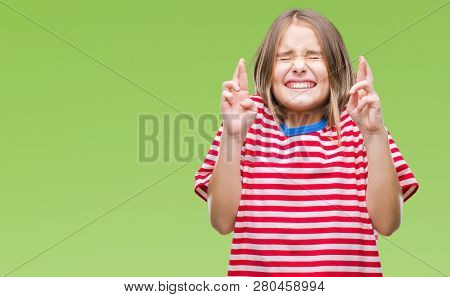 Young beautiful girl over isolated background smiling crossing fingers with hope and eyes closed. Luck and superstitious concept.