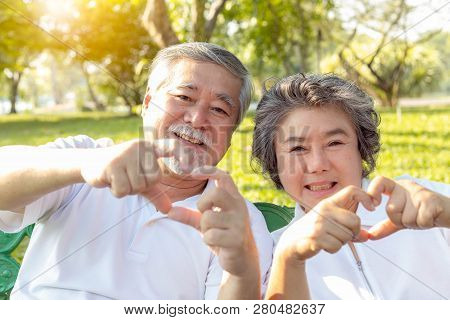 Grandma And Grandpa Or Grandparents Make Symbol Of Love By Using Hands And Fingers For Making Hearts