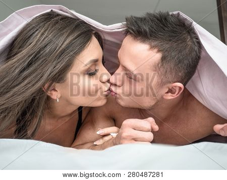 Handsome Kissing Couple Under A Duvet In The Bed. Happy Young Couple Lying Down Comfortably In Their