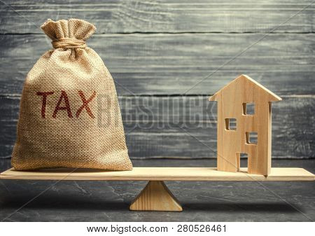 Wooden House And A Money Bag With The Word Tax On The Scales. Taxes On Real Estate, Payment. Registe