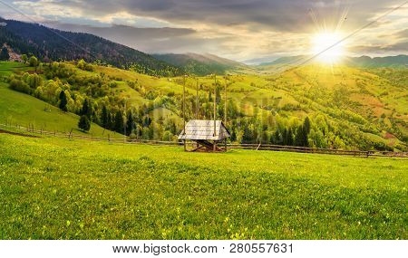 Hay Shed On A Grassy Field In Mountains. Beautiful Countryside Landscape In Springtime At Sunset In