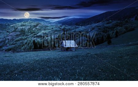 Hay Shed On A Grassy Field In Mountains. Beautiful Countryside Landscape In Springtime At Night In F