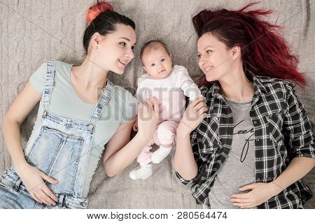 Two Young Women, A Lesbian Homosexual Couple, Are Lying On A Blanket With A Child. Same-sex Marriage