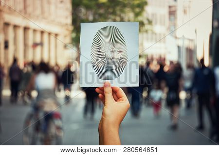 Hand Holding A Paper Sheet With Fingerprint Icon Over A Crowded Street Background. Concept Of Social