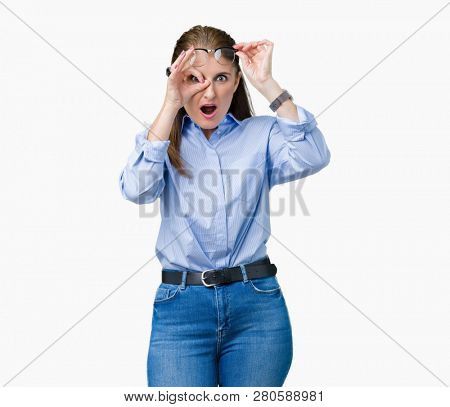 Beautiful middle age mature business woman wearing glasses over isolated background doing ok gesture shocked with surprised face, eye looking through fingers. Unbelieving expression.